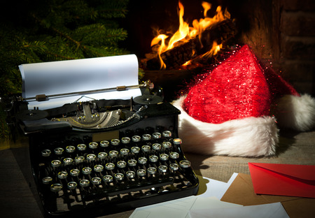 34381198 - old typewriter and santa claus hat on desk in front of fireplace